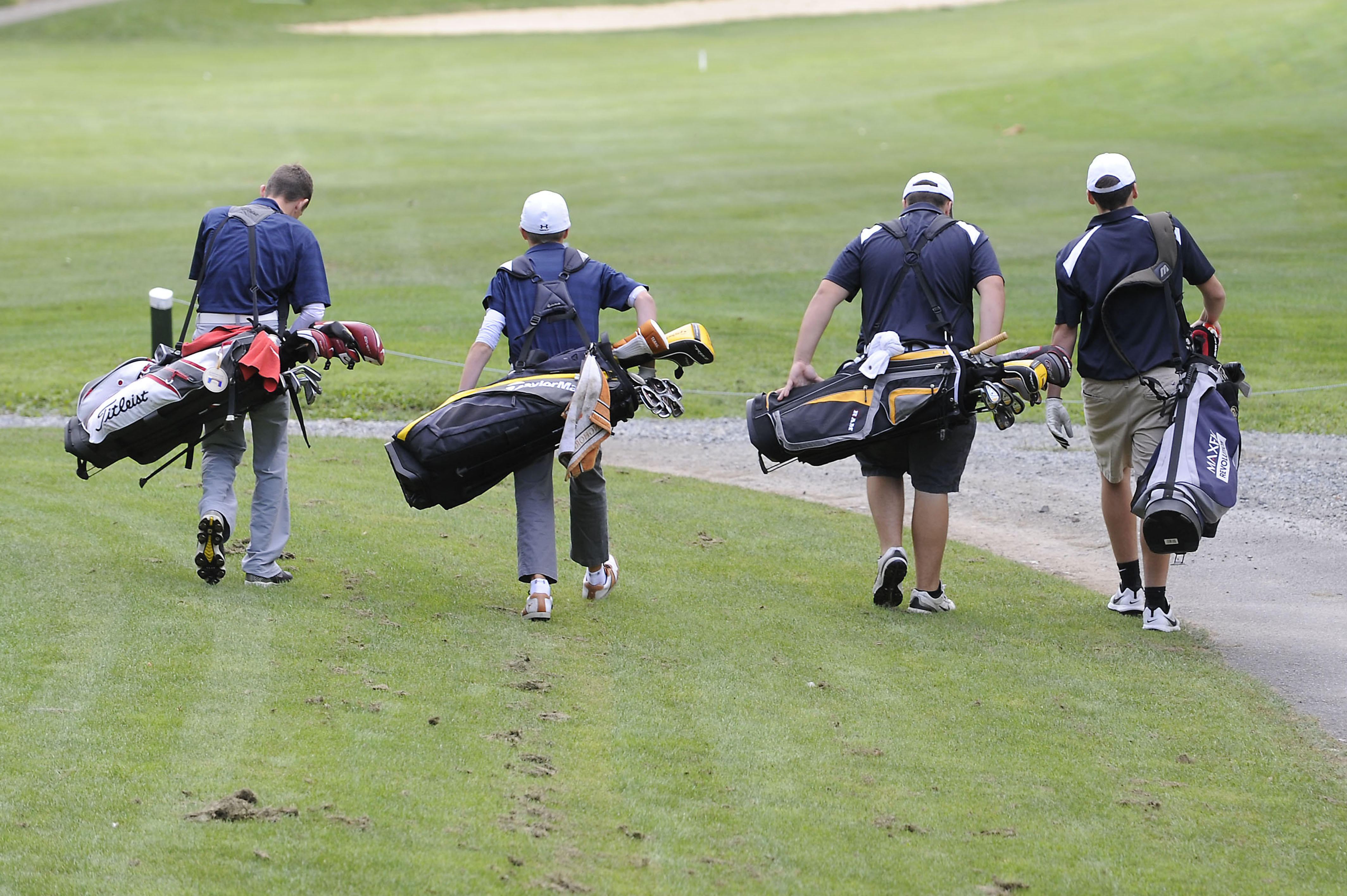 4 golfers walking with clubs